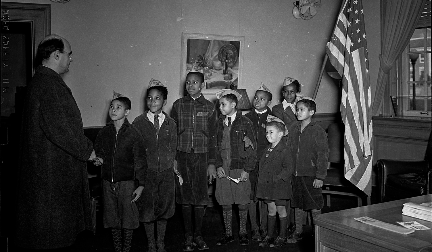 "[Mordecai Johnson (?) with a group of boys wearing hats with ""BOSTON TRAVELER"" printed on them, in room with American flag] [cellulose acetate photonegative]"