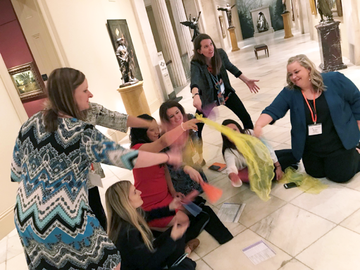 Teachers on the floor of a museum learning about wind